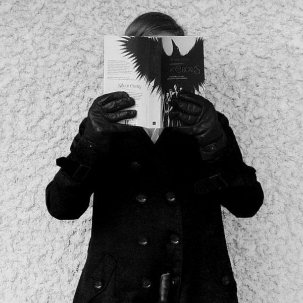 personne en noir et blanc lisant Six of Crows de Leigh Bardugo