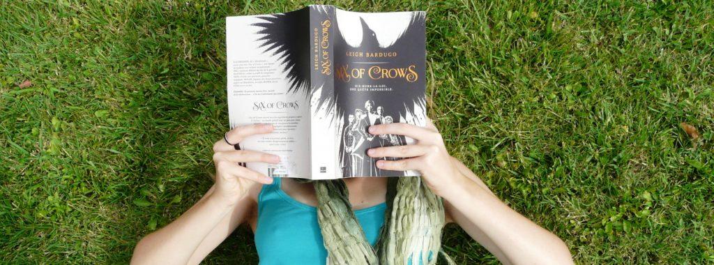 personne en débardeur vert lisant Six of Crows dans l'herbe