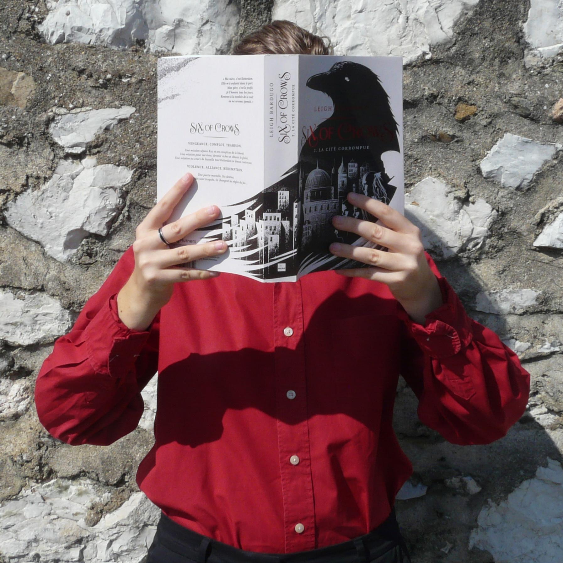 personne en chemise rouge lisant La Cité Corrompue devant un mur de pierres