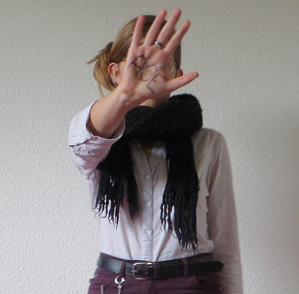personne cachant son visage avec une main sur laquelle est écrit ACE