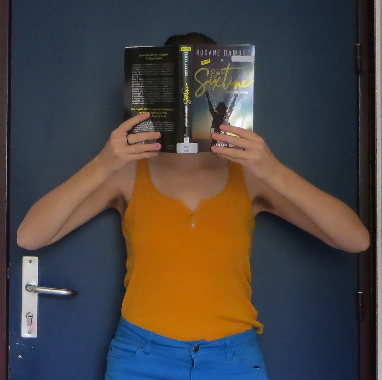 personne en jaune lisant Signé Sixtine de Roxane Dambre devant sa porte