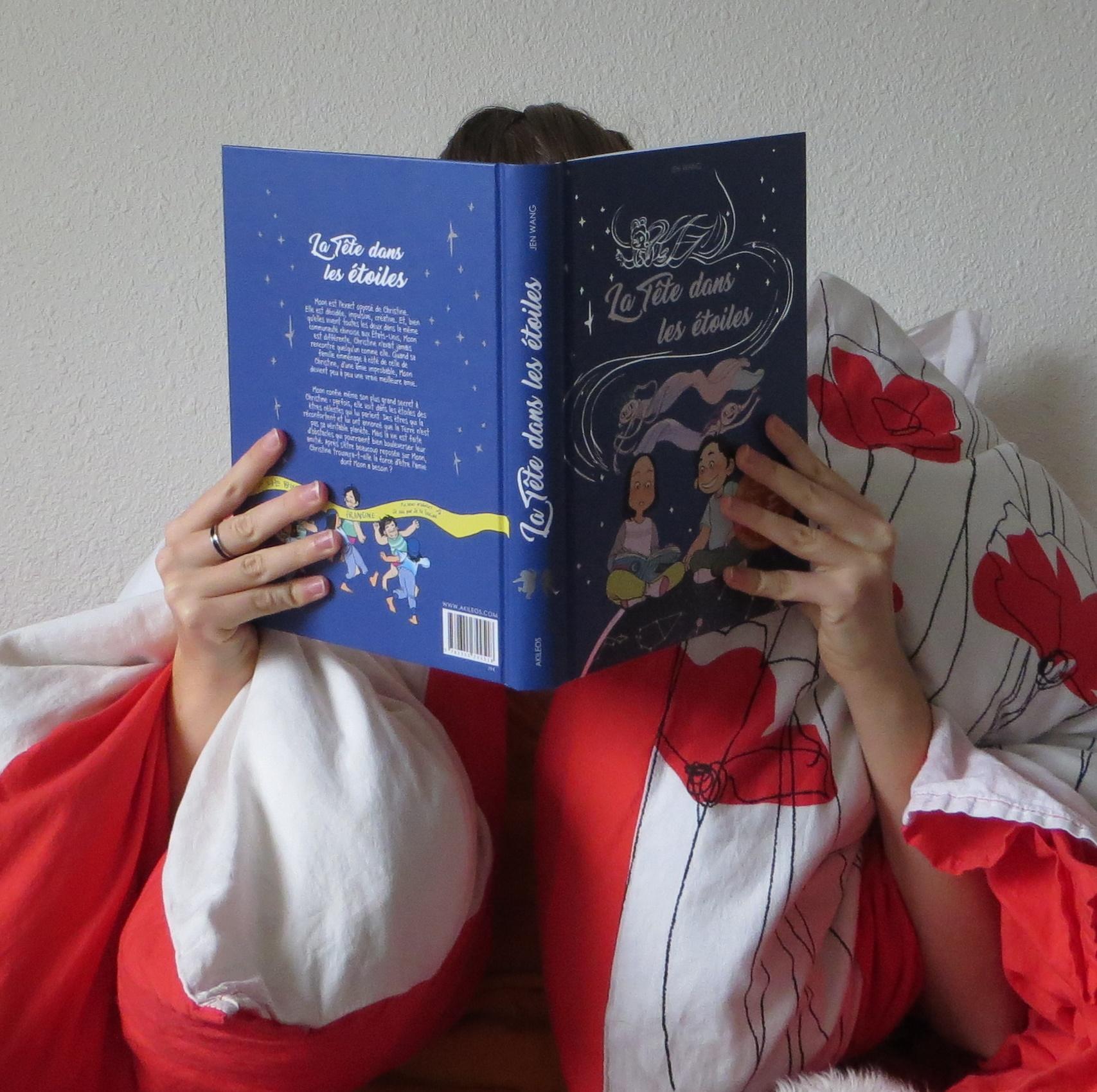 personne lisant La tête dans les étoiles, blottie dans une couverture