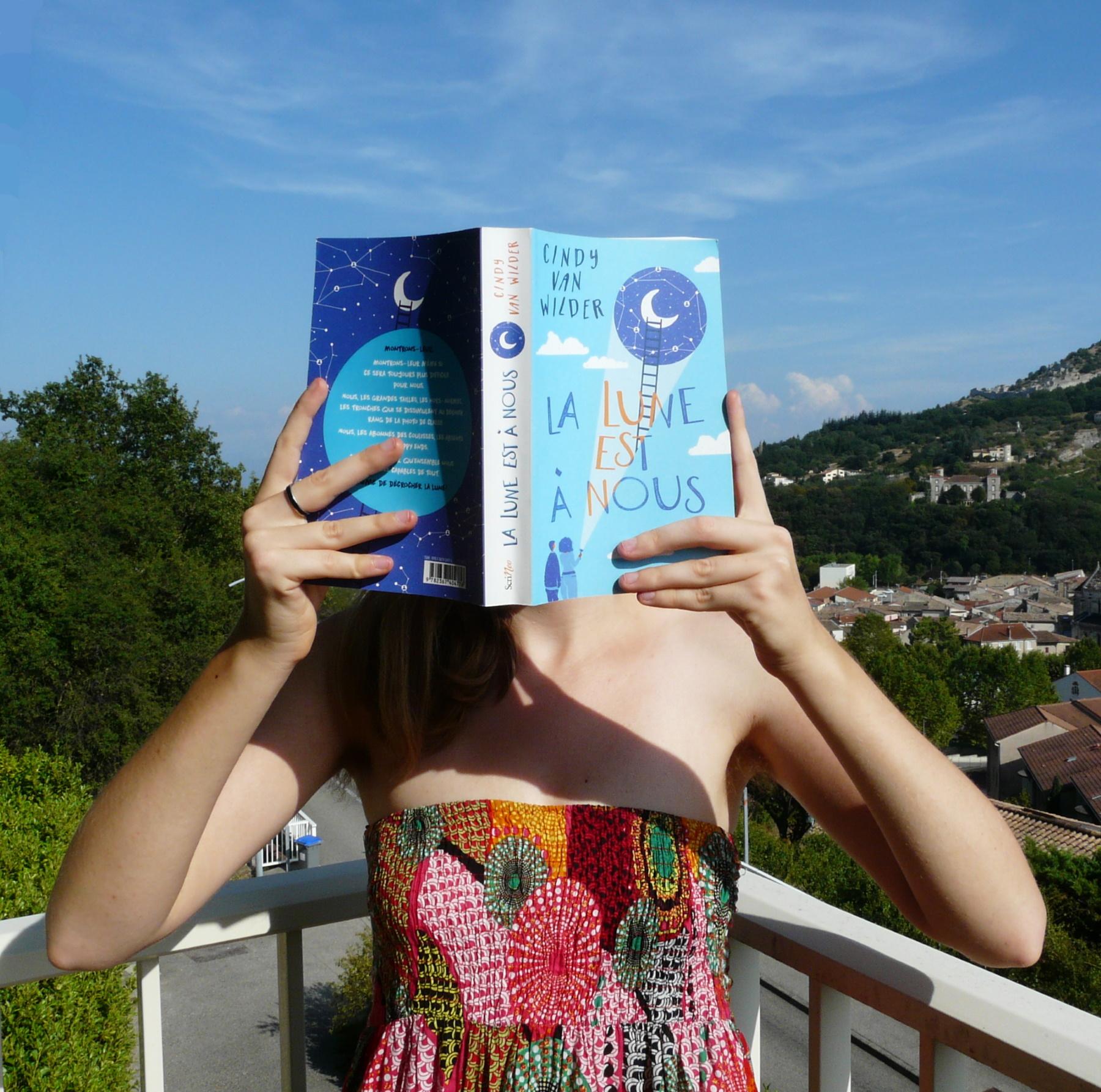 personne en robe multicolore lisant La Lune est à nous en haut d'une colline