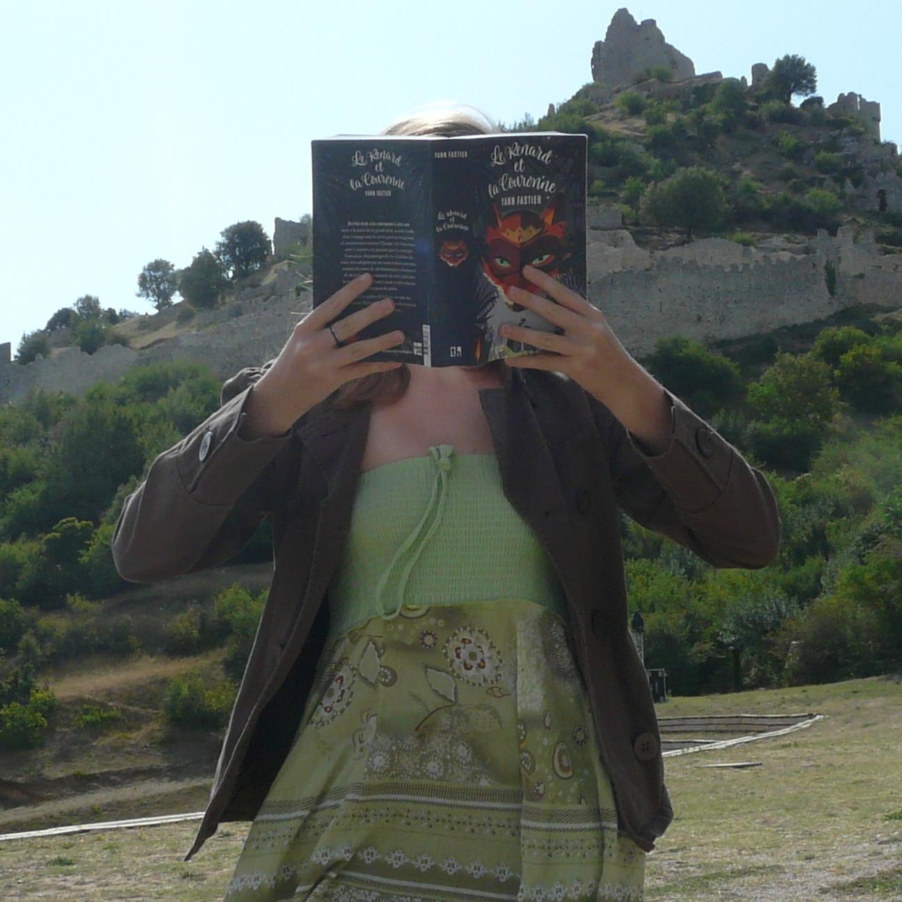 femme en robe verte et veste marron lisant Le Renard et la Couronne devant une ruine, les cheveux agités par le vent