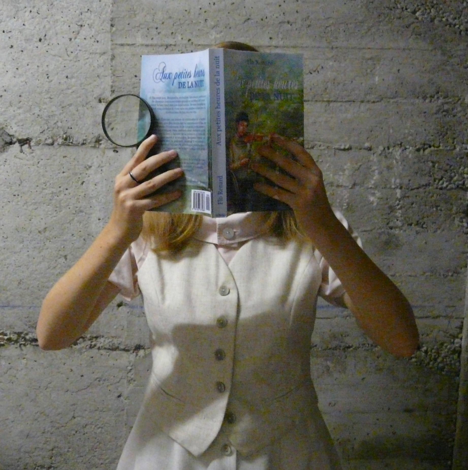 femme en tailleur démodé lisant Aux Petites Heures de la nuit dans une cave mal éclairée, une loupe à la main