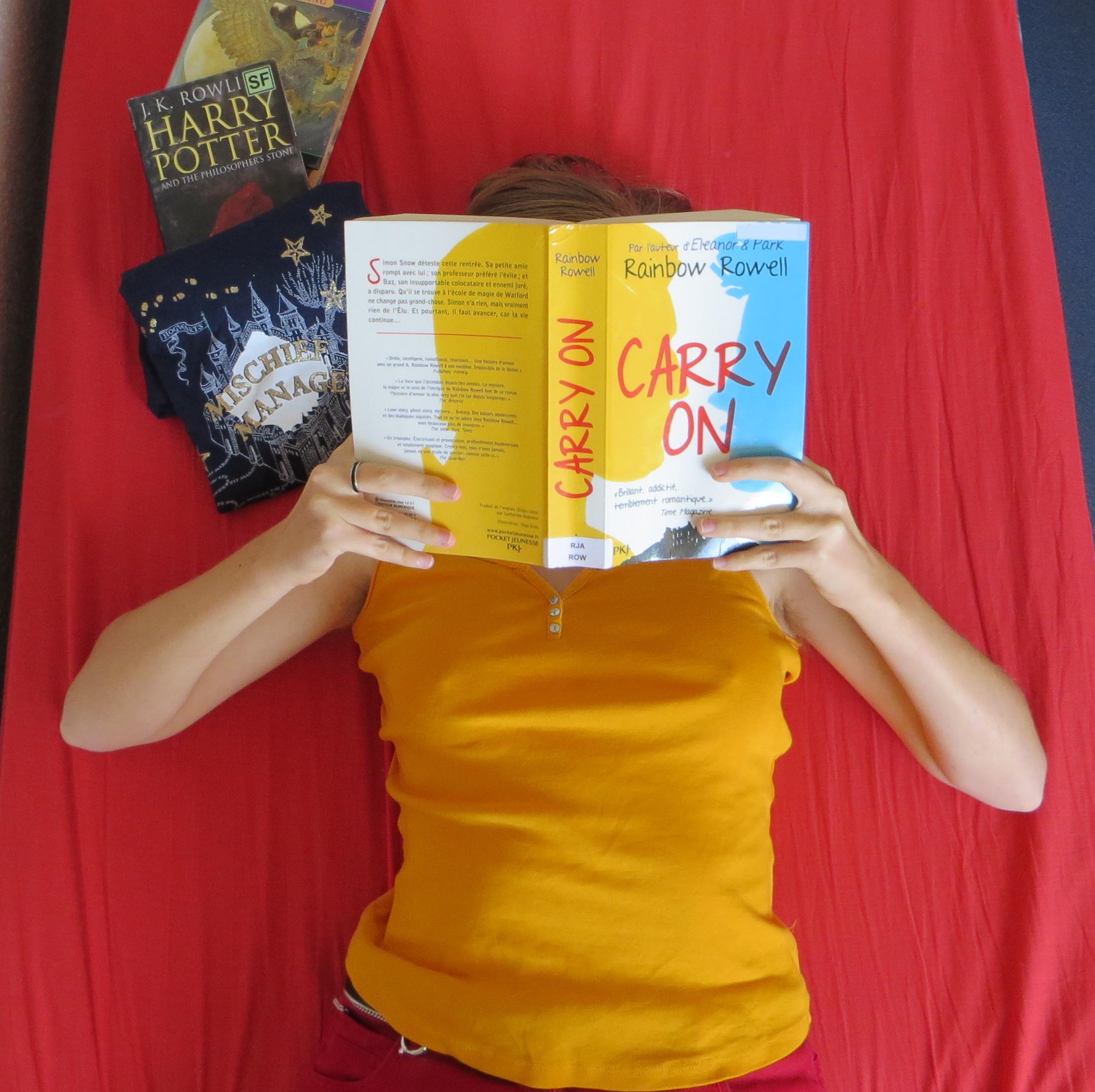 femme en débardeur doré lisant Carry On de Rainbow Rowell, allongée sur un lit rouge avec des tomes de Harry Potter et un pyjama Harry Pottes à côté
