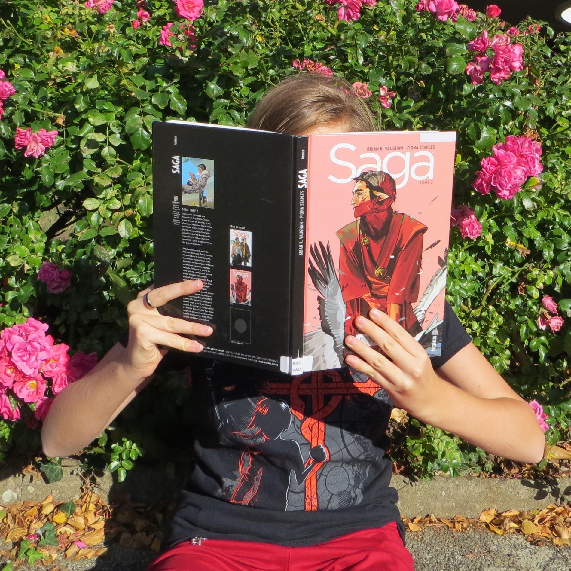 femme lisant la BD Saga de Brian K. Vaughan et Fiona Staples devant un buisson de roses