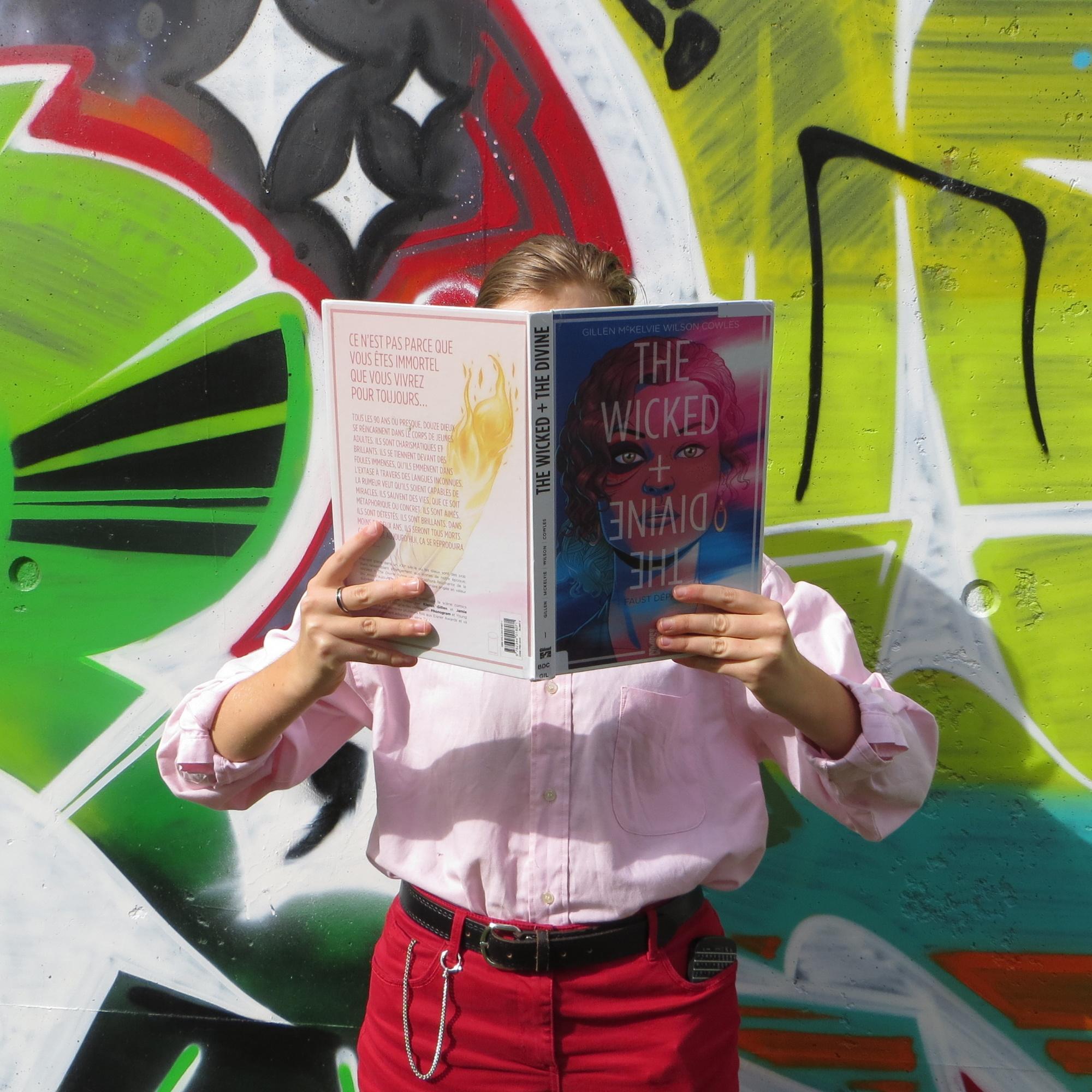 personne en chemise rose lisant The Wicked + The divine de Kieron Gillen et Jamie McKelvie devant un tag coloré