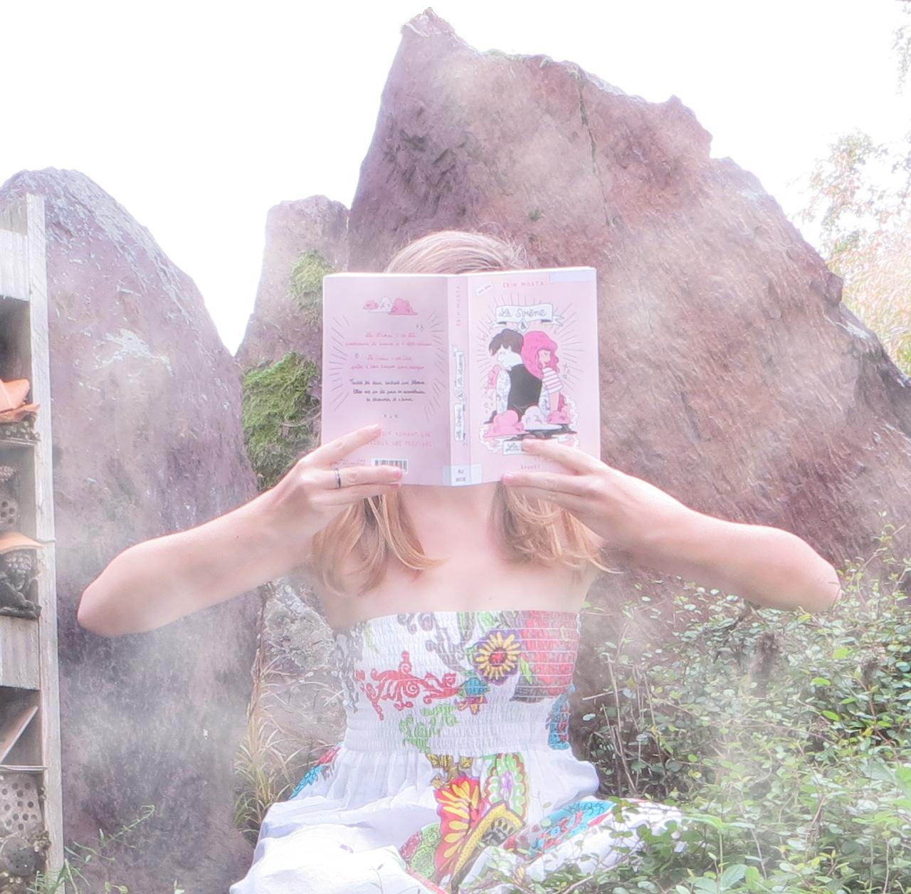 Entre des rochers, dans la brume, femme en sarouel coloré lisant La Sirène & La Licorne d'Erin Mosta