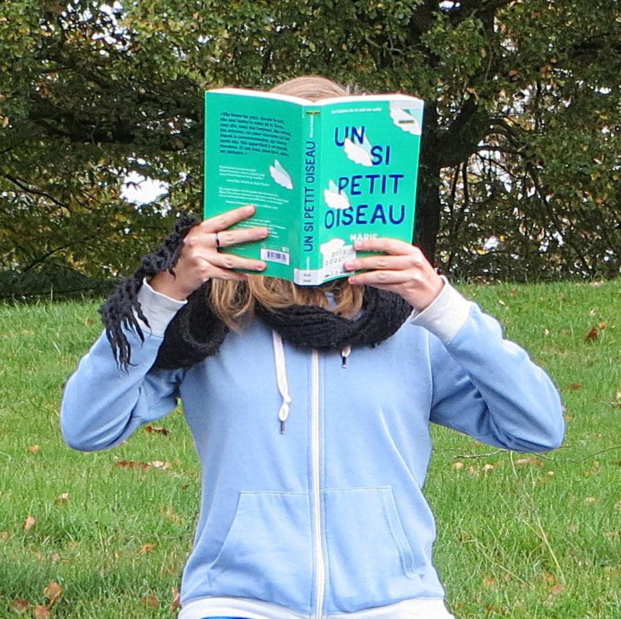 femme en gilet bleu lisant Un si Petit Oiseau dans l'herbe