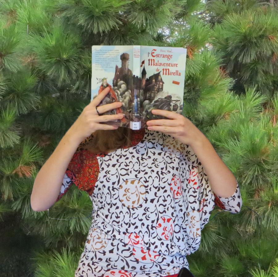 femme avec un t-shirt asymétrique lisant l'Estrange Malaventure de Mirella devant des sapins