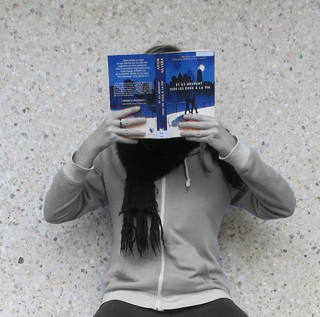 femme en noir et blanc lisant Et ils Meurent tous les deux à la Fin d'Adam Silvera, le roman est en couleurs