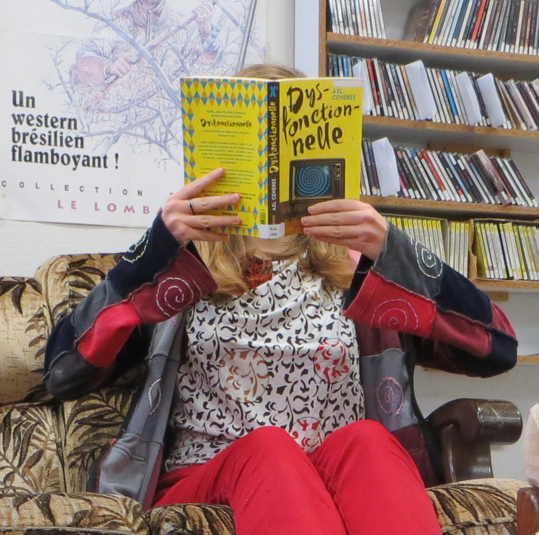 femme lisant Dysfonctionnelle d'Axl Cendres dans une bibliothèque vieillotte
