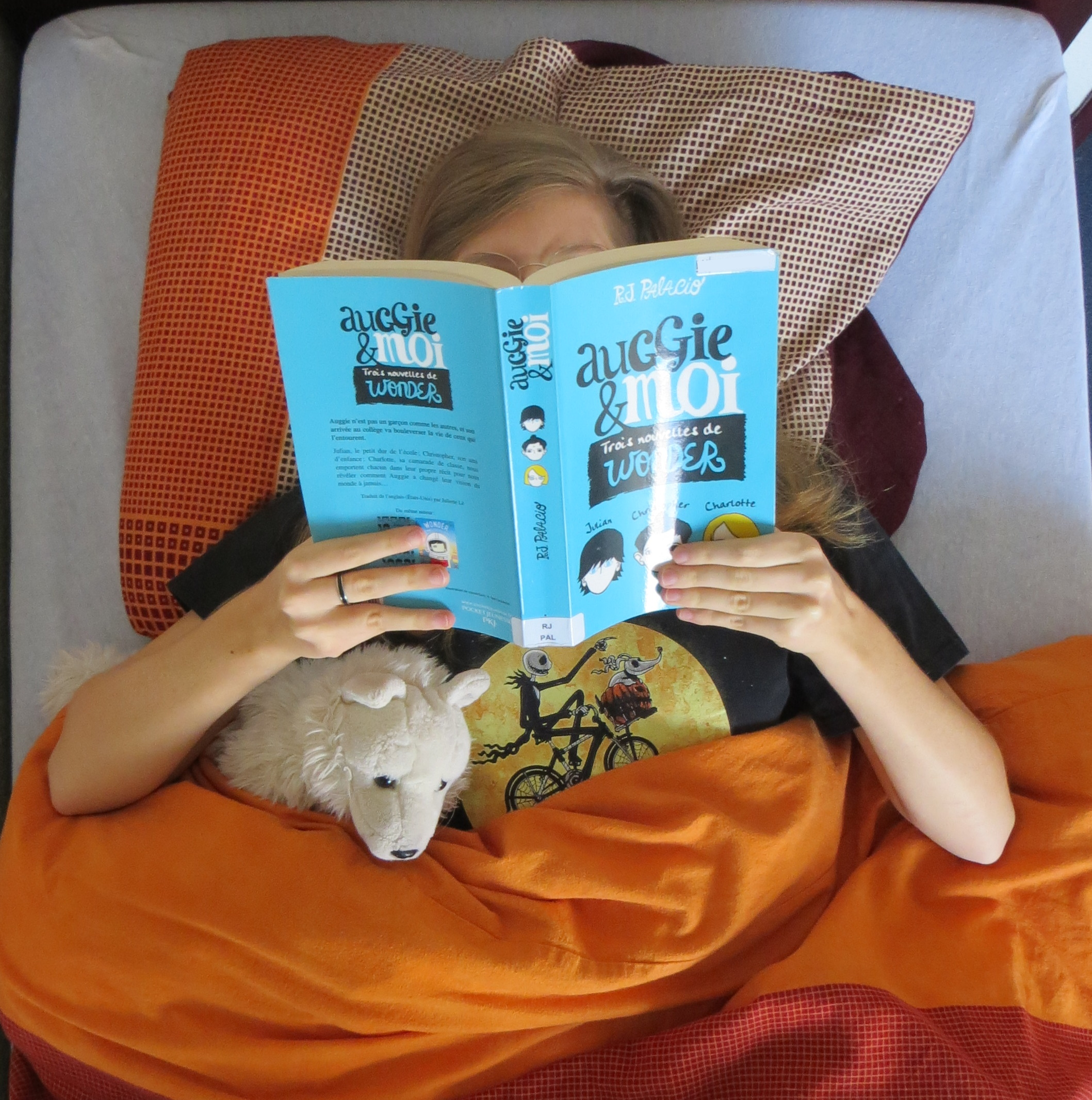 Dans un lit avec une couverture orange, femme lisant Auggie & moi de RJ Palacio