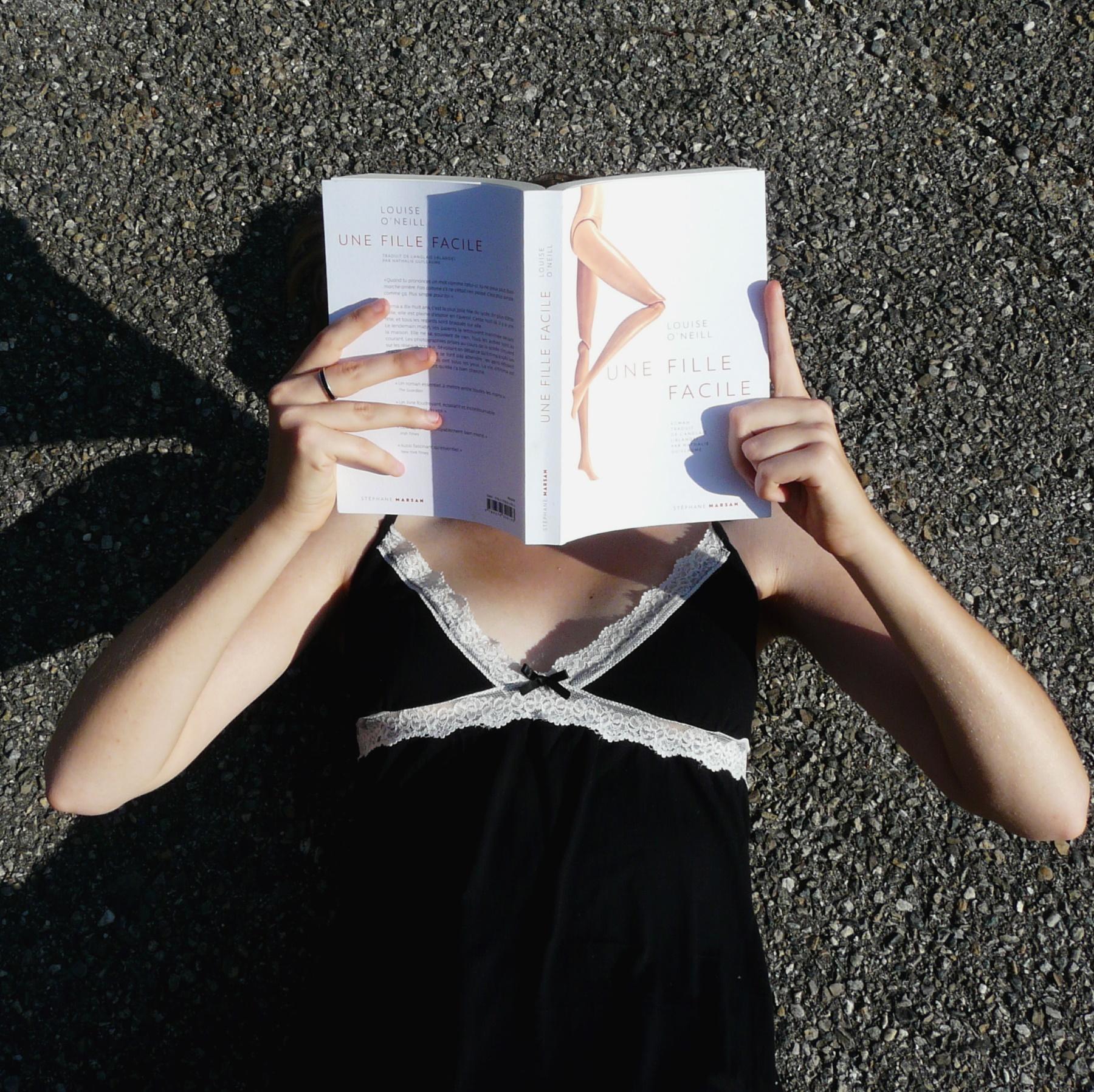 femme en nuisette lisant une fille facile allongée sur du goudron