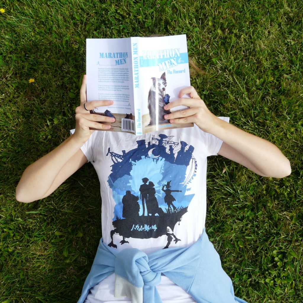 femme en t-shirt Le Château Ambulant lisant Marathon Men de Flo Renard allongée dans l'herbe