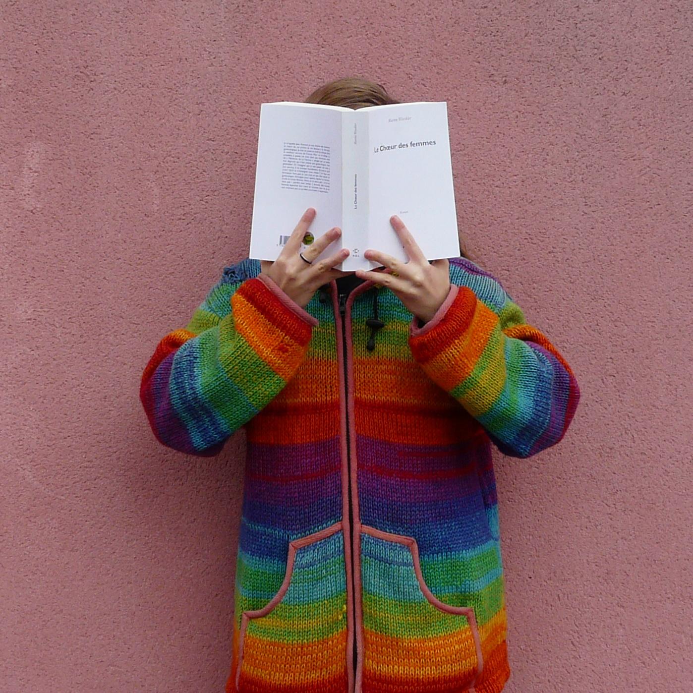 femme en manteau multicolore lisant Le chœur des Femmes devant un mur rose