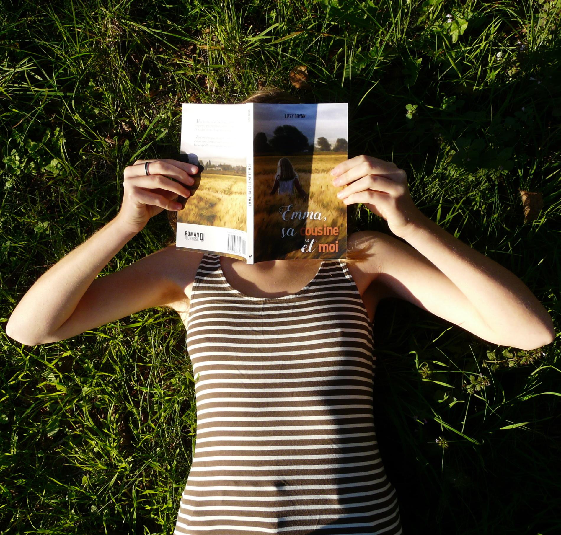 femme en débardeur rayé lisant Emma, sa Cousine et Moi de Lizzy Brynn dans l'herbe