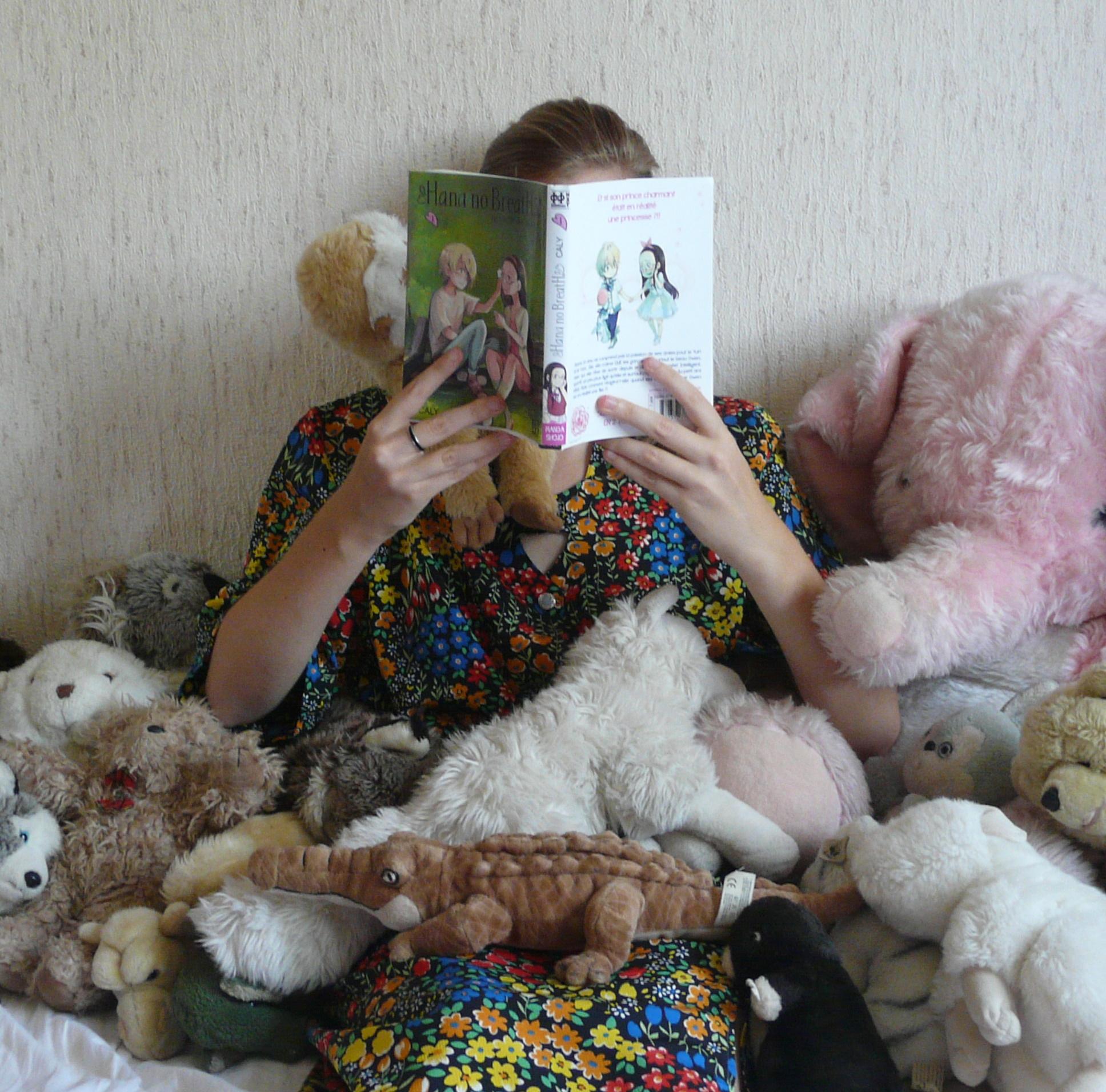 femme en robe à fleurs multicolores lisant Hana No Breath tome 1 de Caly, au milieu de plein de peluches