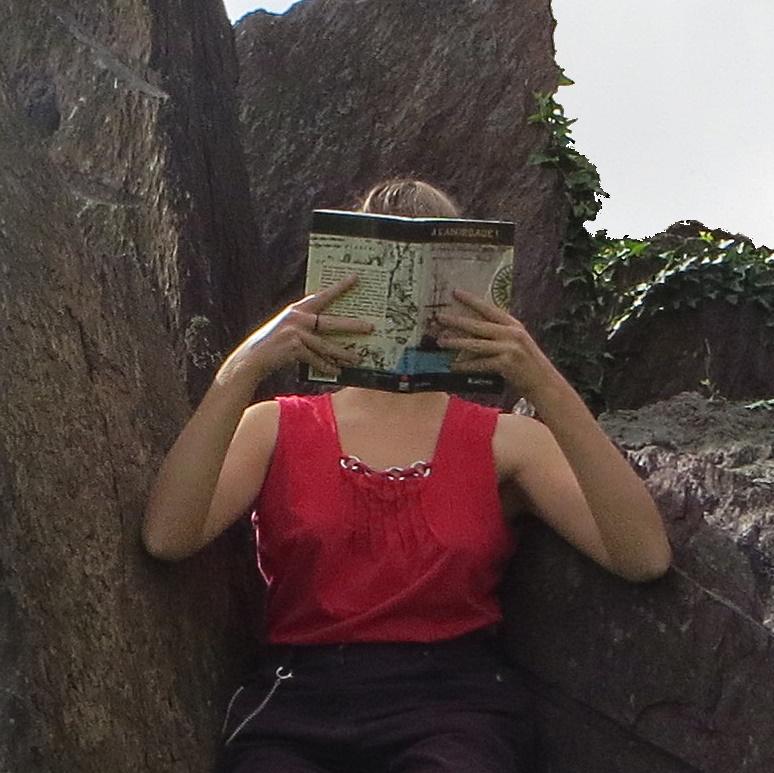 femme en débardeur rouge lisant A l'abordage de Kadyan devant des rochers