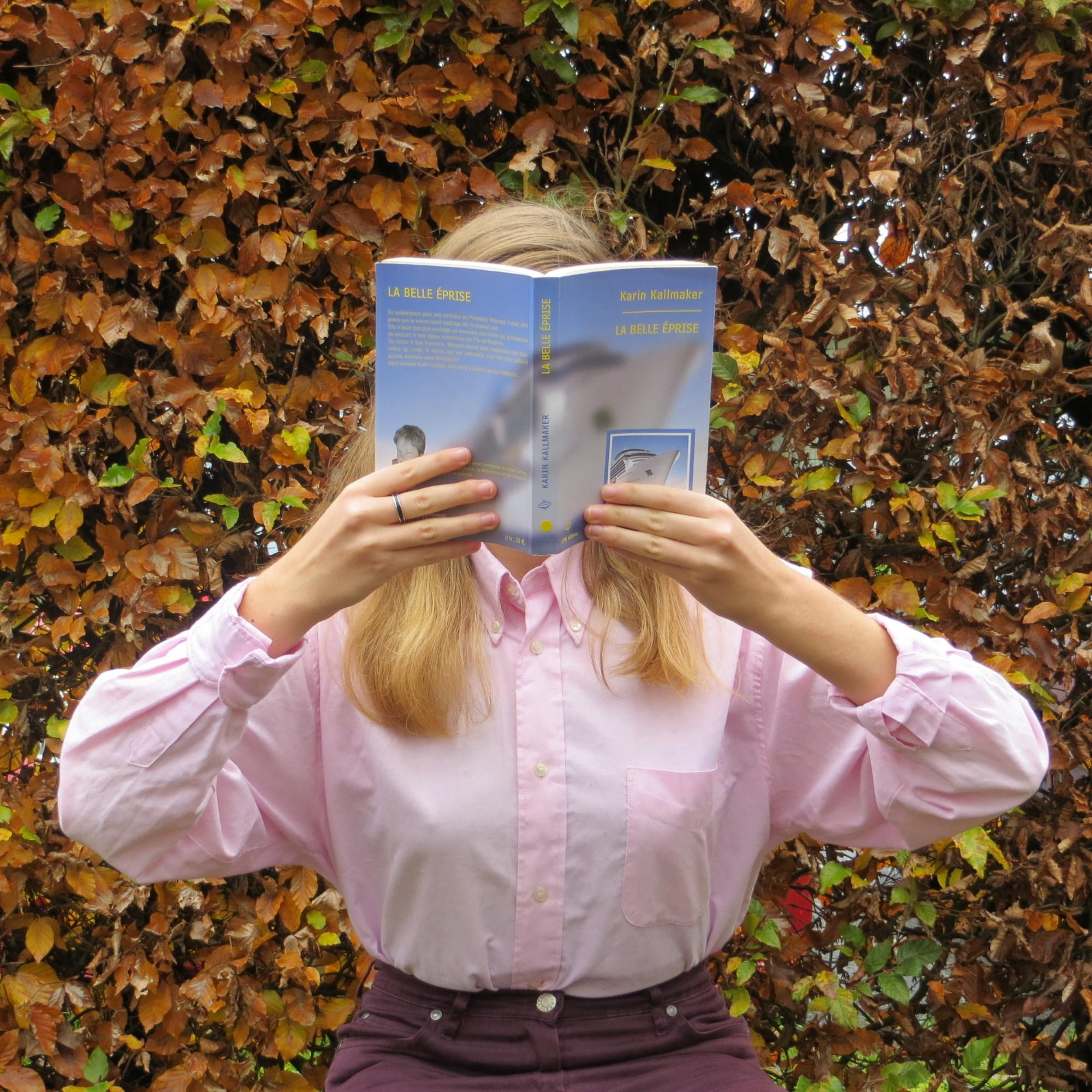personne en chemise rose lisant La Belle Eprise de Karin Kallmaker devant une haie d'automne