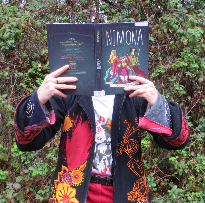 femme en manteau et t-shirt à flammes lisant la BD Nimona devant un mur de ronces