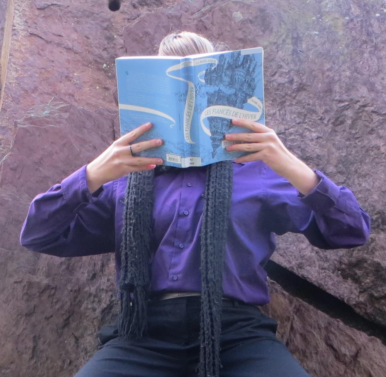 personne en chemise violette lisant Les Fiancés de l'Hiver devant un mur de roche rouge