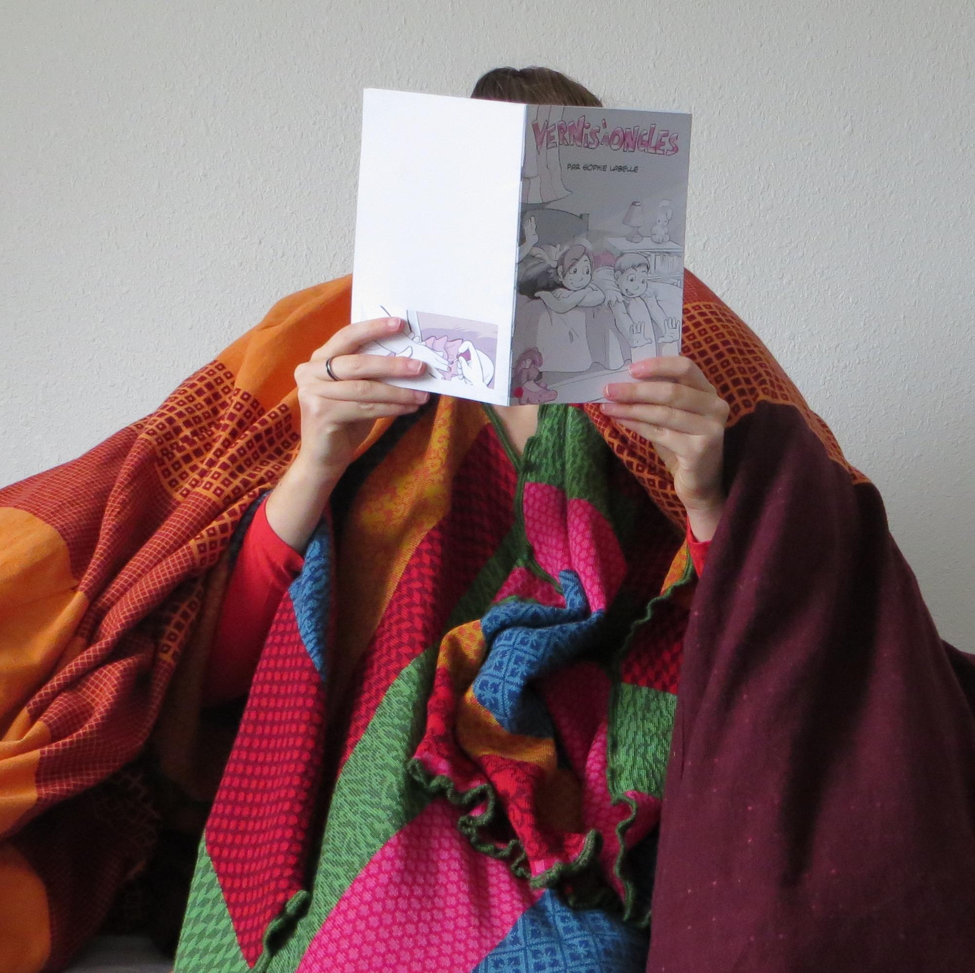 femme lisant Vernis à ongle entourée de sa couverture et d'un plaid