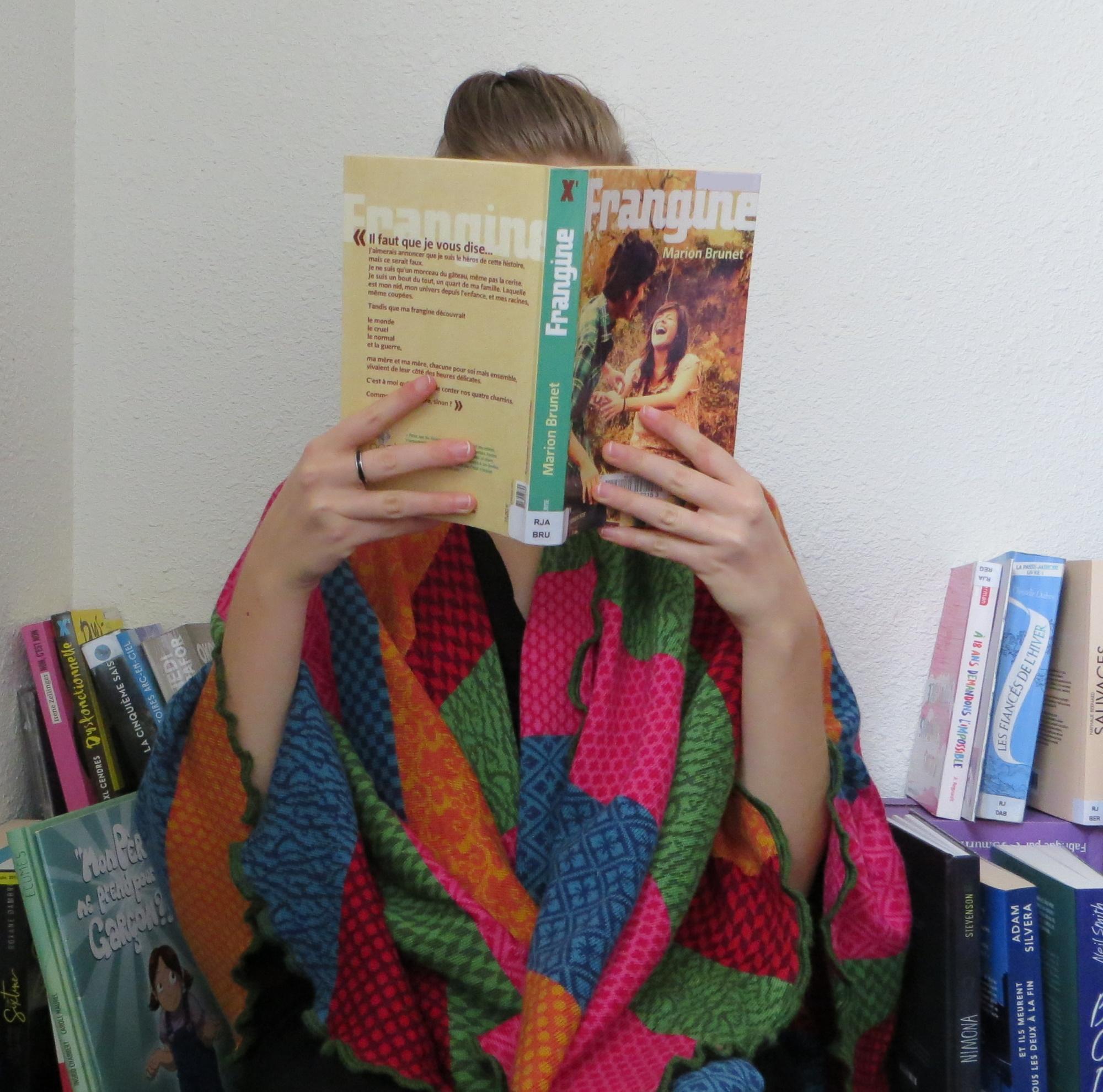 femme lisant Frangine devant une étagère, les épaules recouvertes d'un plaid multicolore