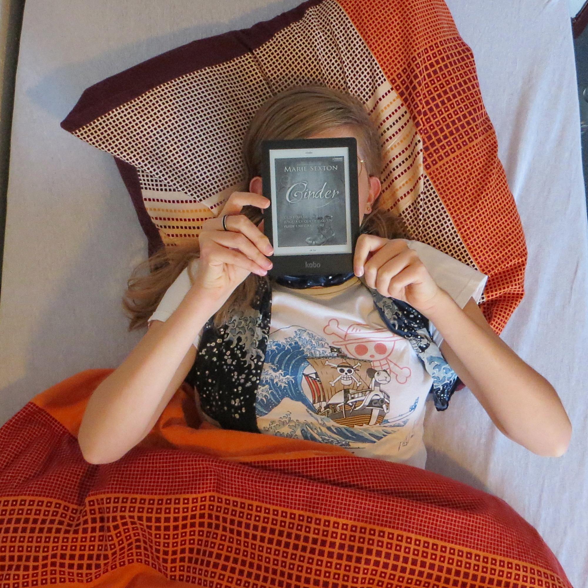 femme lisant Cinder dans son lit