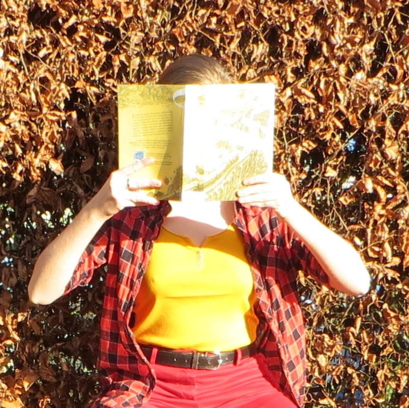 photo surexposée d'une personne en débardeur et chemise lisant un livre méconnaissable (la passe-miroir tome 2) devant une haie automnale