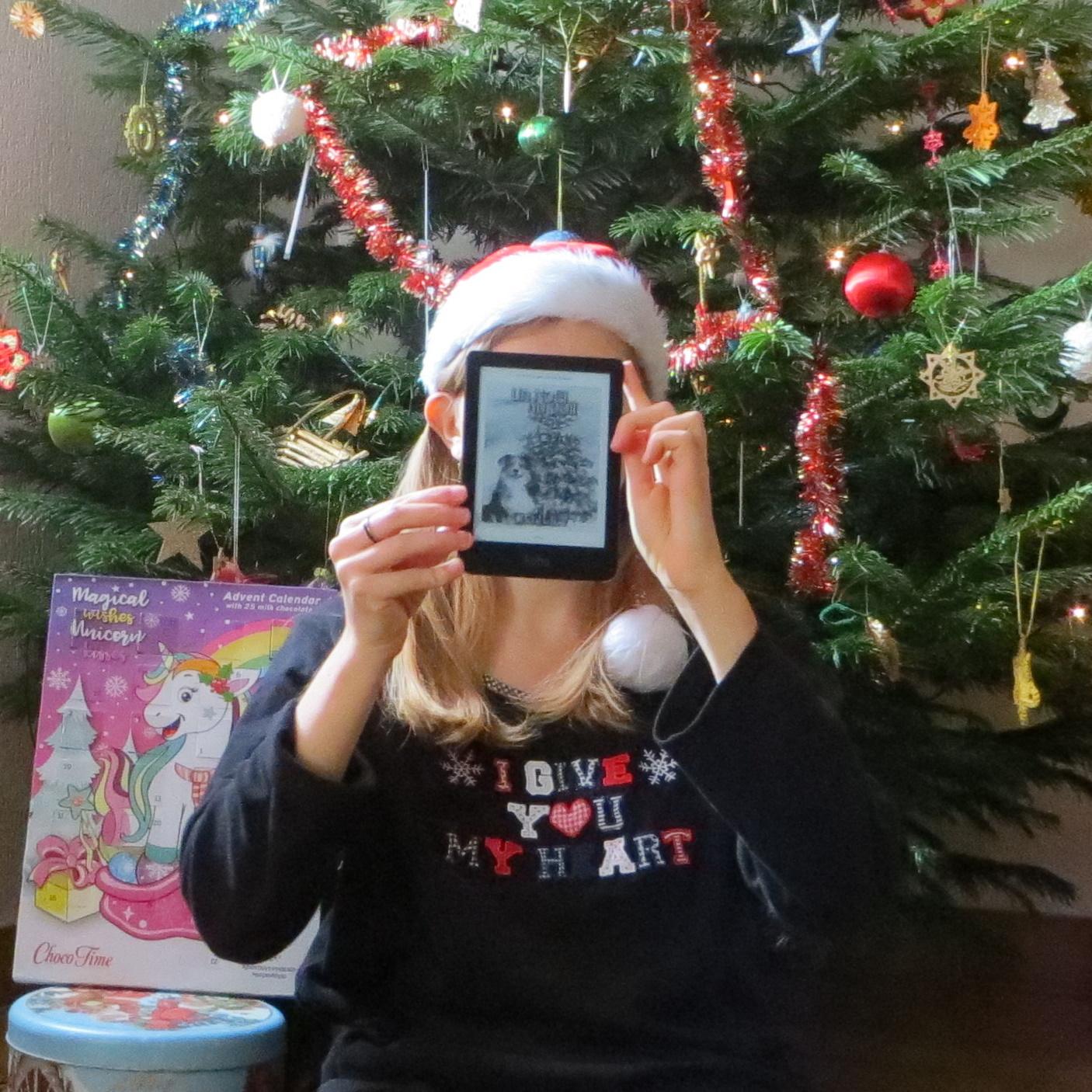 femme en bonnet rouge et haut de Noël brandissant sa liseuse avec la couverture de Un Noël au Poil, devant un sapin et un calendrier de l'Avent Licorne