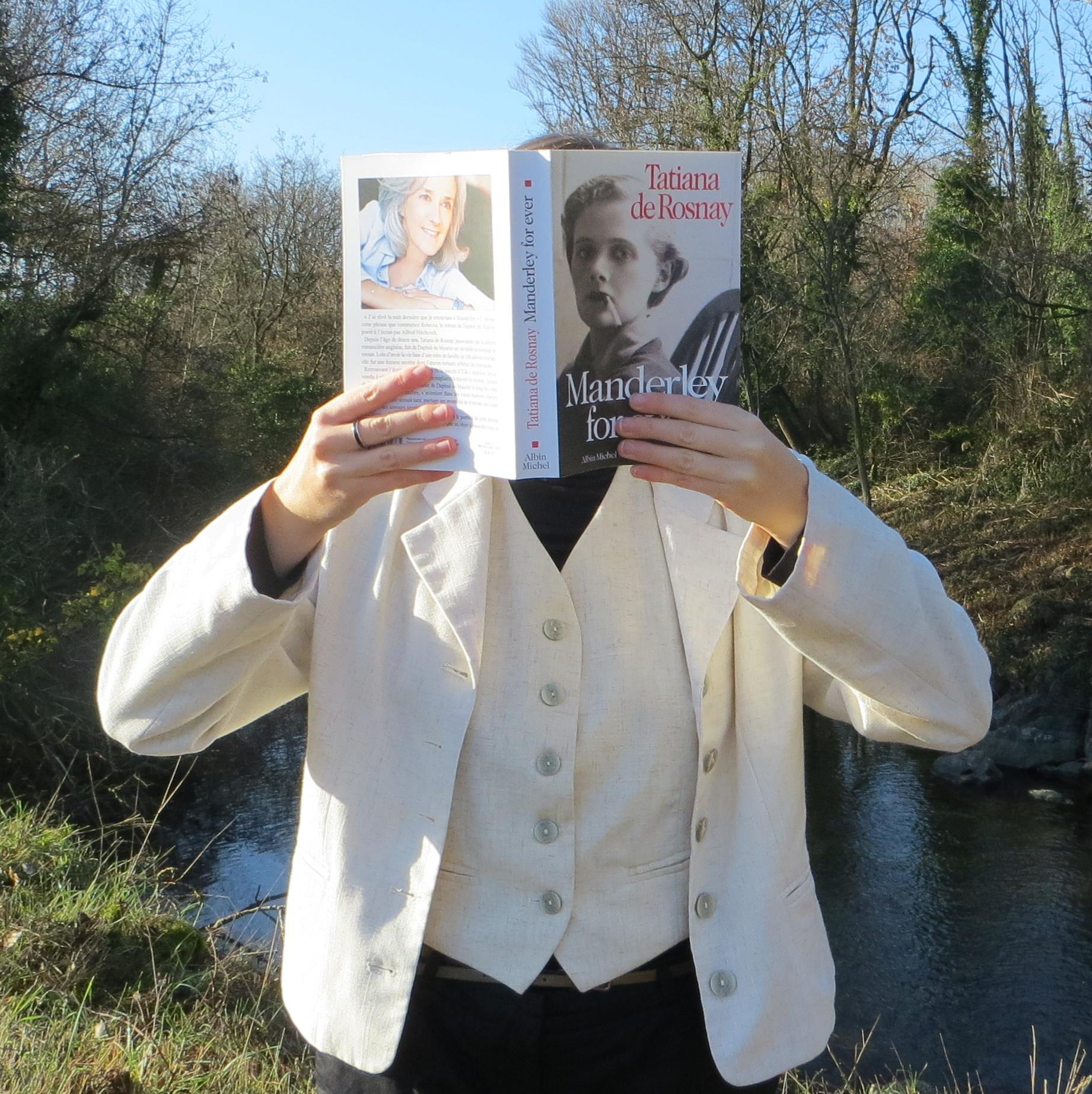 femme en costume beige lisant Manderley Forever devant une rivière et une forêt sauvages