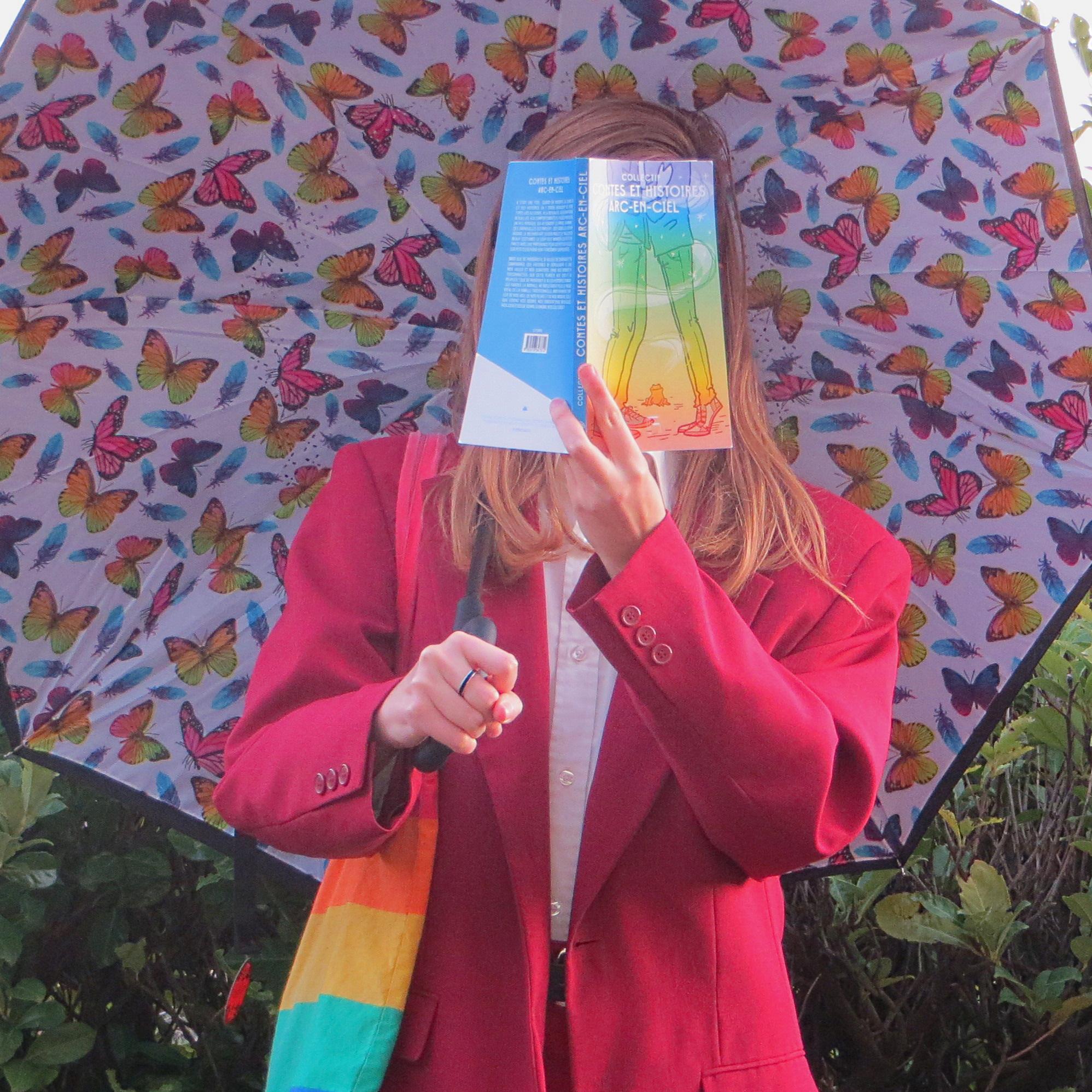 femme en costume rouge tenant un parapluie à papillons multicolores, un totebag arc-en-ciel, lisant Contes et Histoires Arc-en-ciel devant une haie
