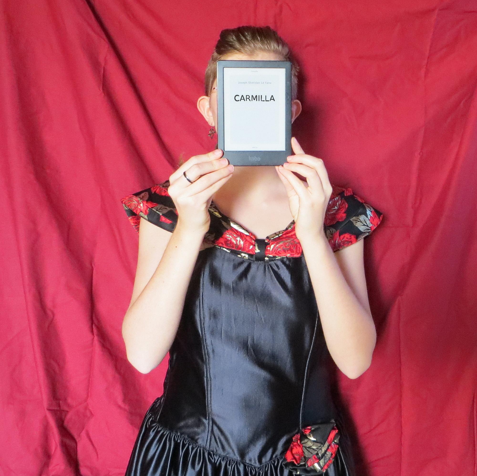 femme en robe bustier noire et rouge, type renaissance, brandissant sa liseuse avec le couverture de Carmilla, devant un drap rouge