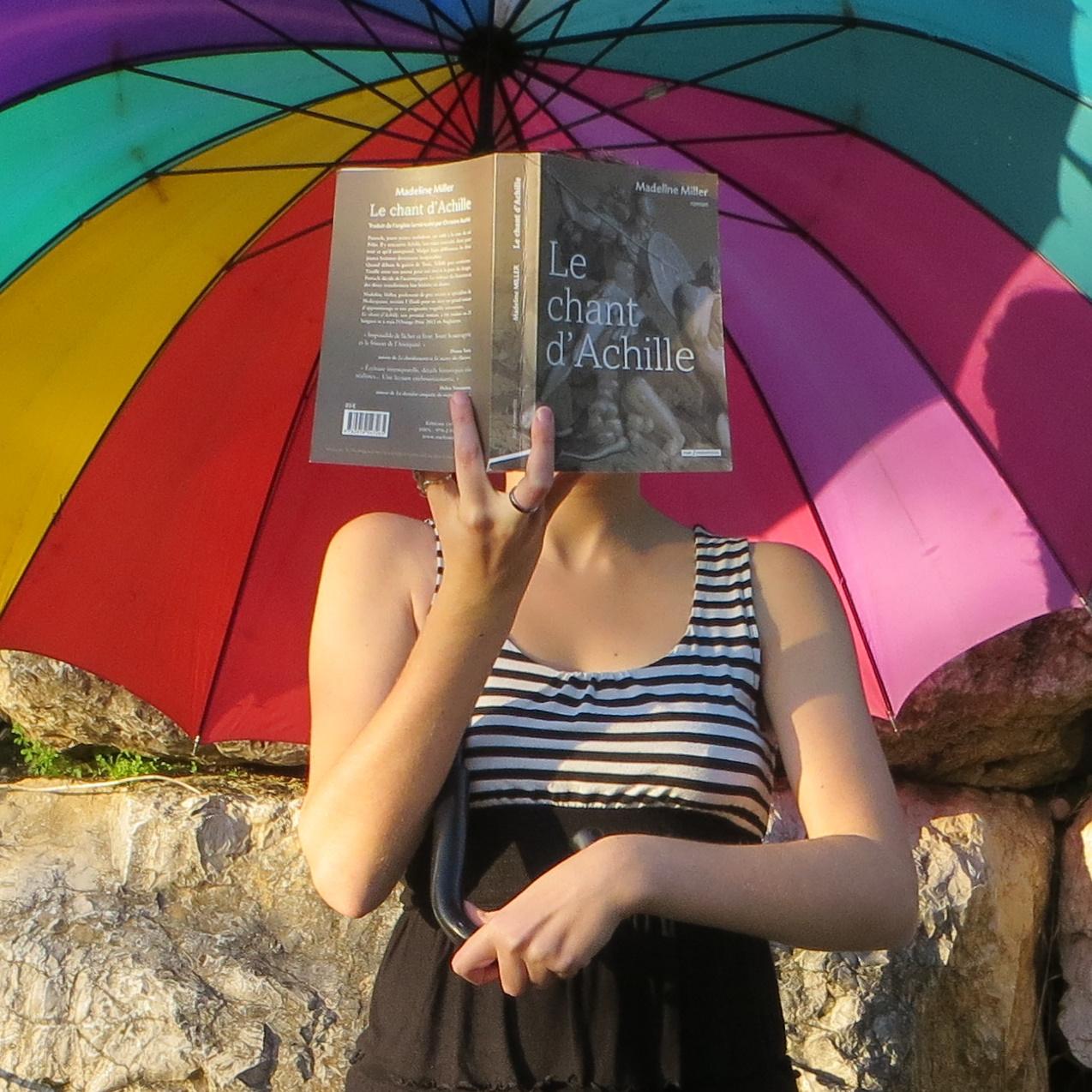 femme en robe noire et blanche avec un parapluie arc-en-ciel lisant Le Chant d'Achille devant un mur de pierre