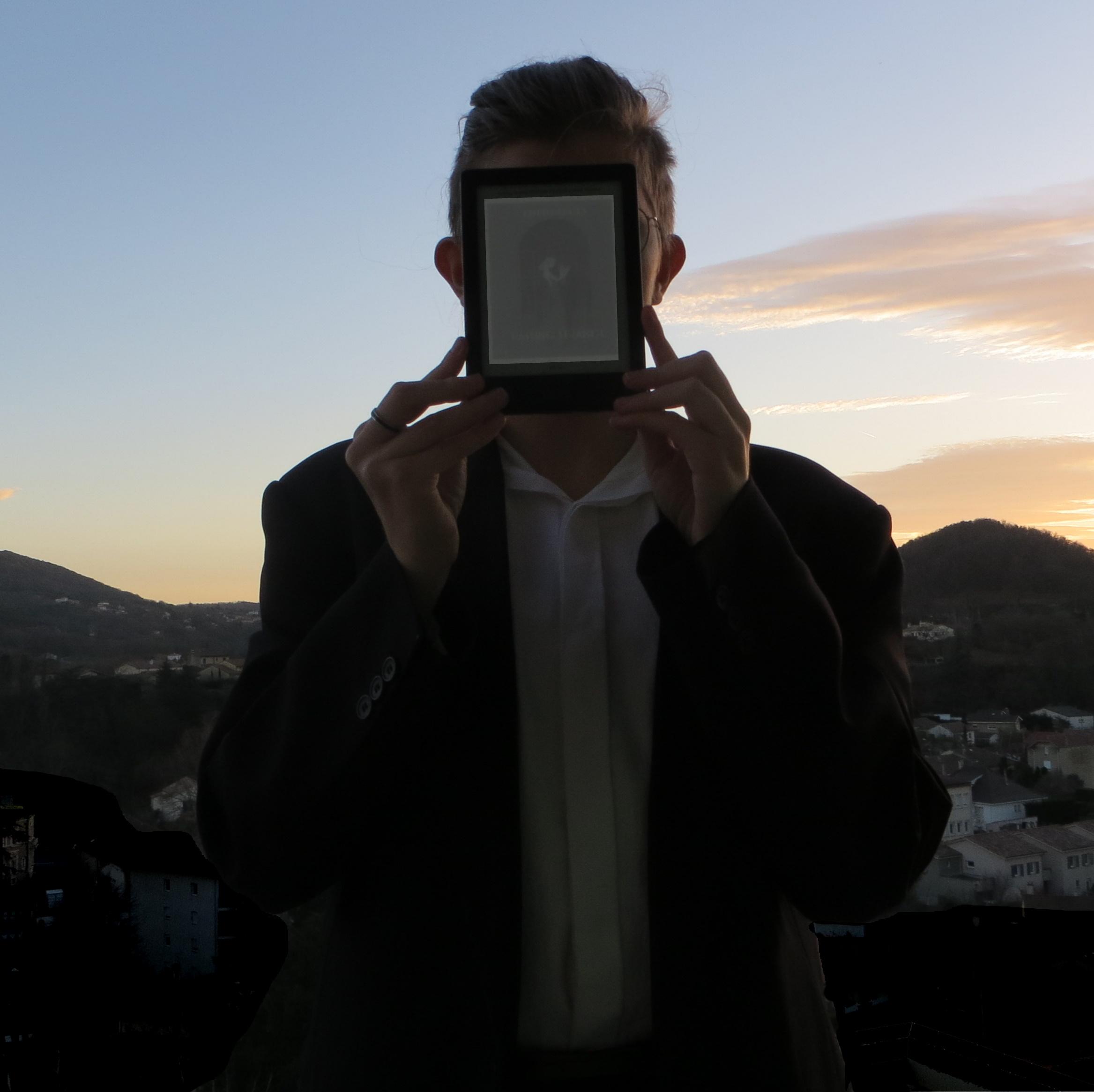 personne en costume, devant le soleil couchant, brandissant sa liseuse avec la couverture de Passing Strange
