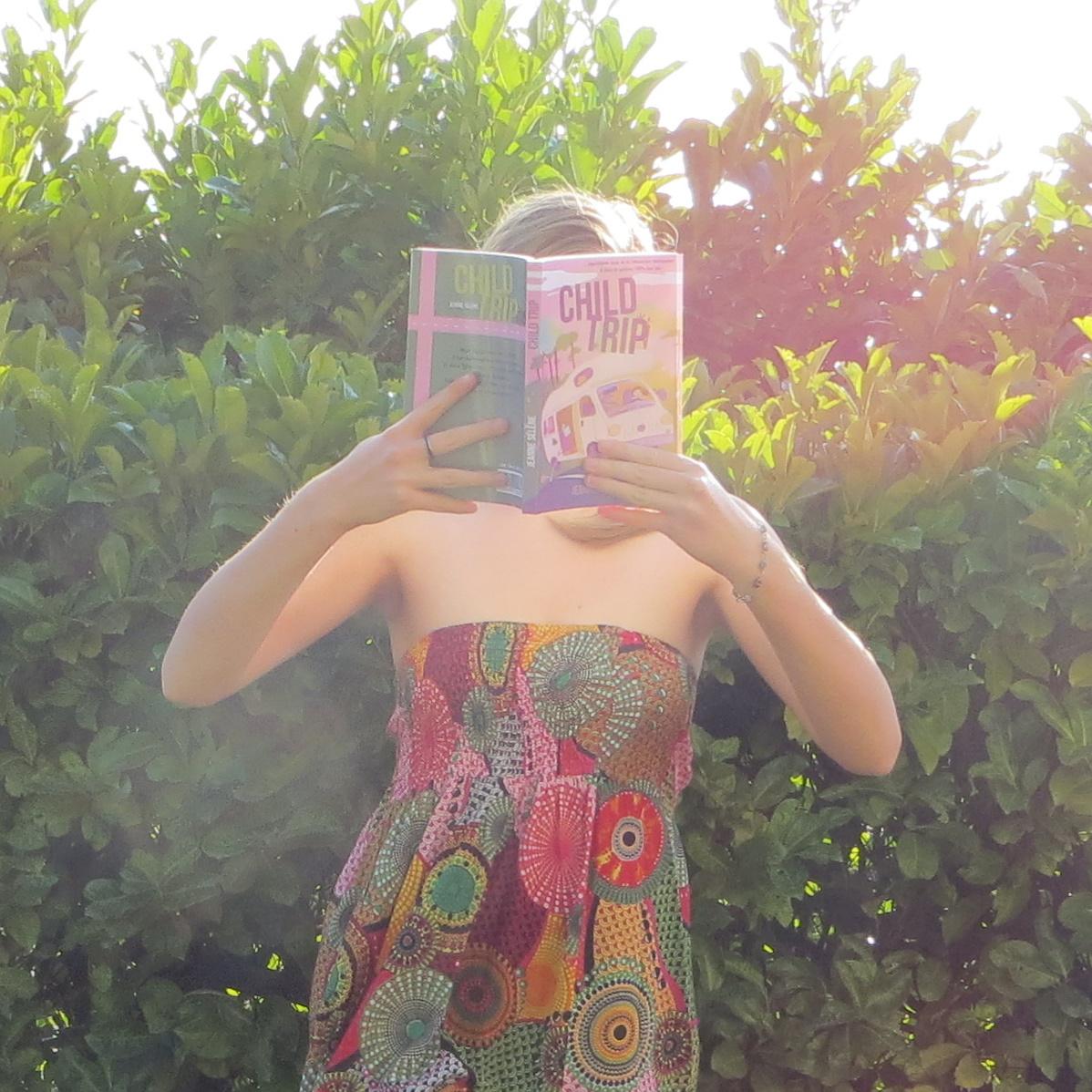 fille en robe bustier multicolore lisant Child Trip de Jeanne Sélène devant une haie, illuminée par le soleil