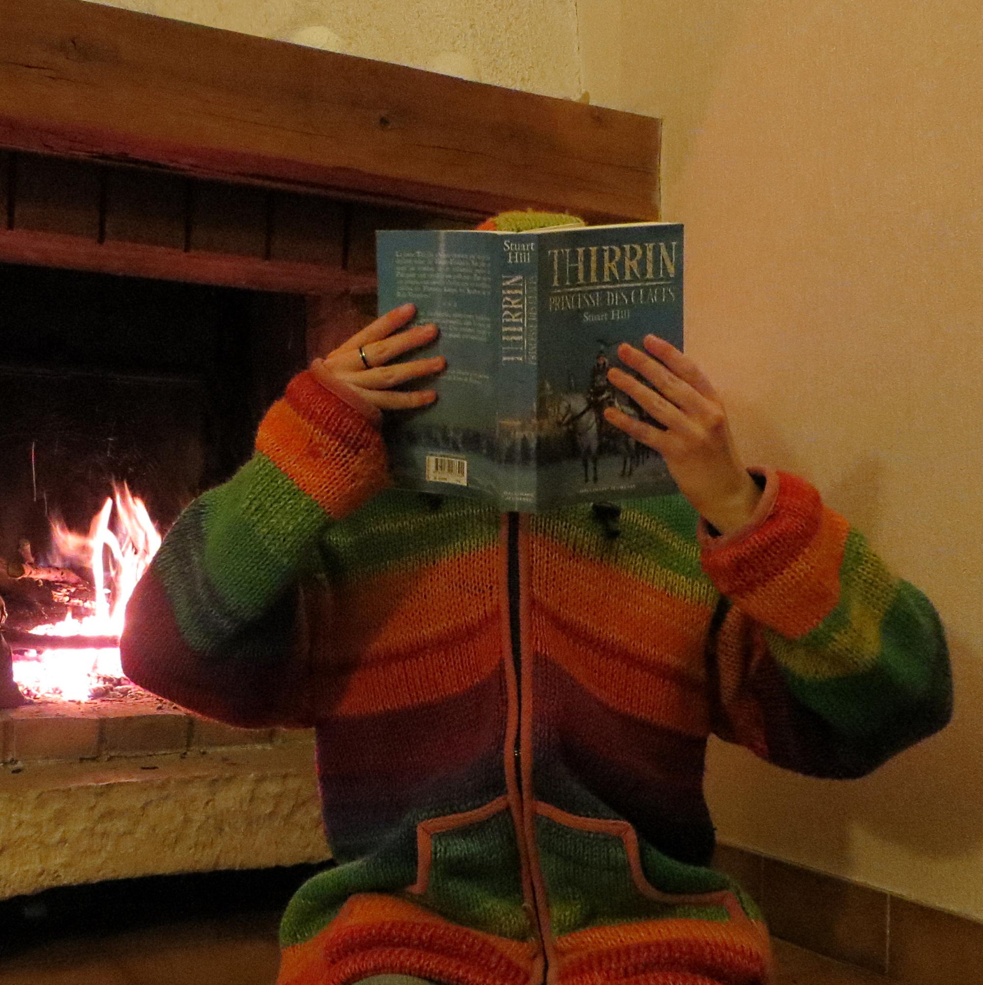 personne en manteau tricoté multicolore lisant Thirrin, Princesse des glaces devant un feu de cheminée