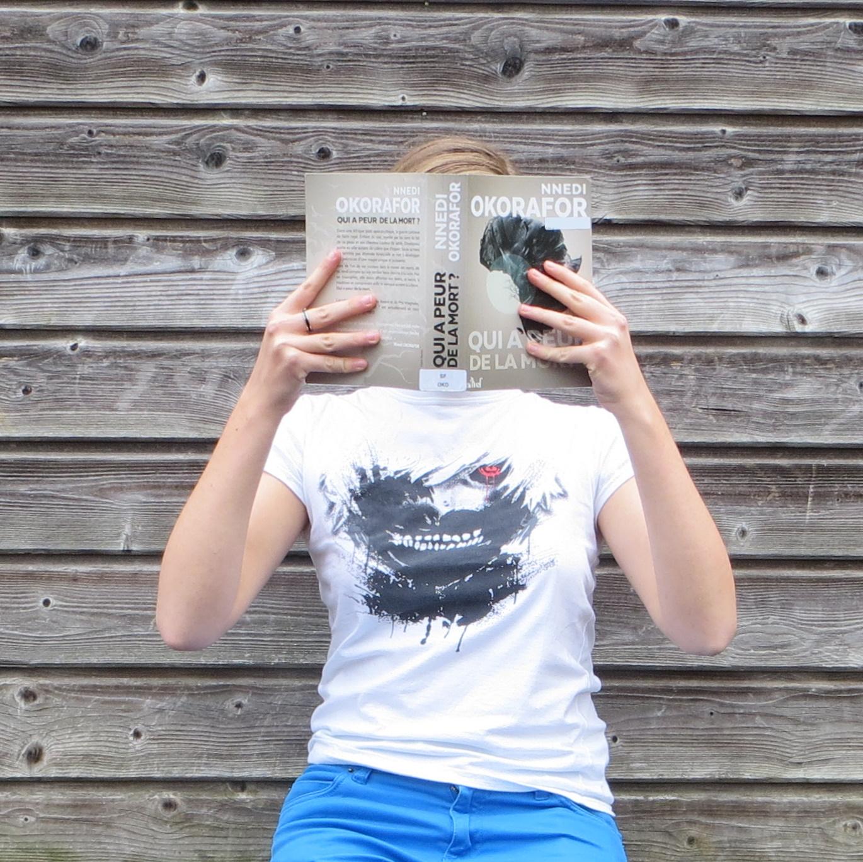 femme en t-shirt Tokyo Ghoul lisant Qui a Peur de la Mort de Nnedi Okorafor devant un mur de planches
