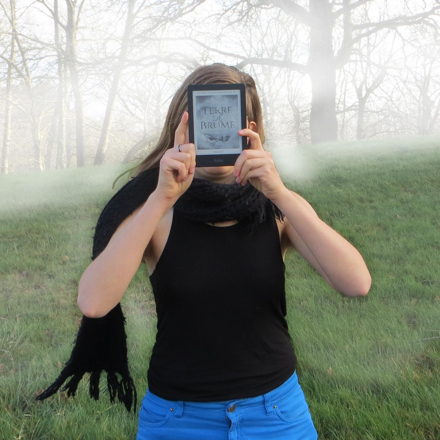 femme en débardeur noir brandissant une liseuse avec la couverture de Terre de Brume, il y a du brouillard et du vent