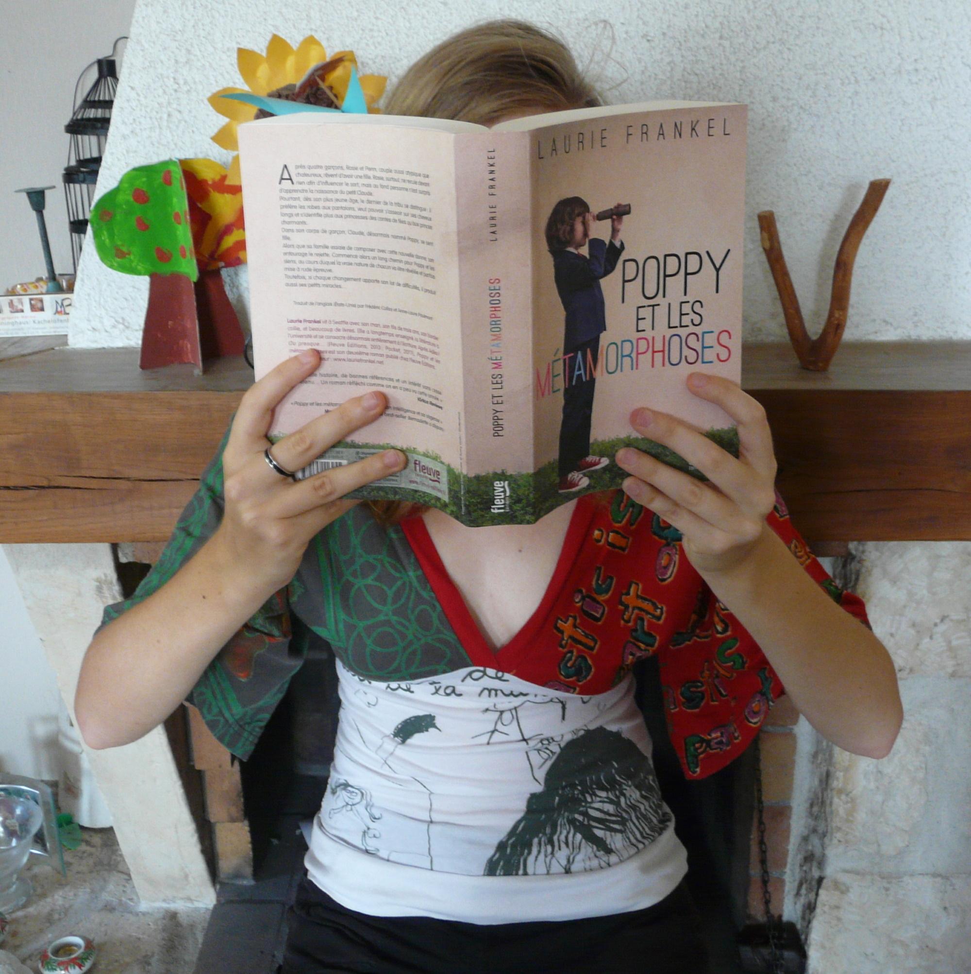 femme lisant Poppy et les métamorphoses de Laurie Frankel devant une cheminée