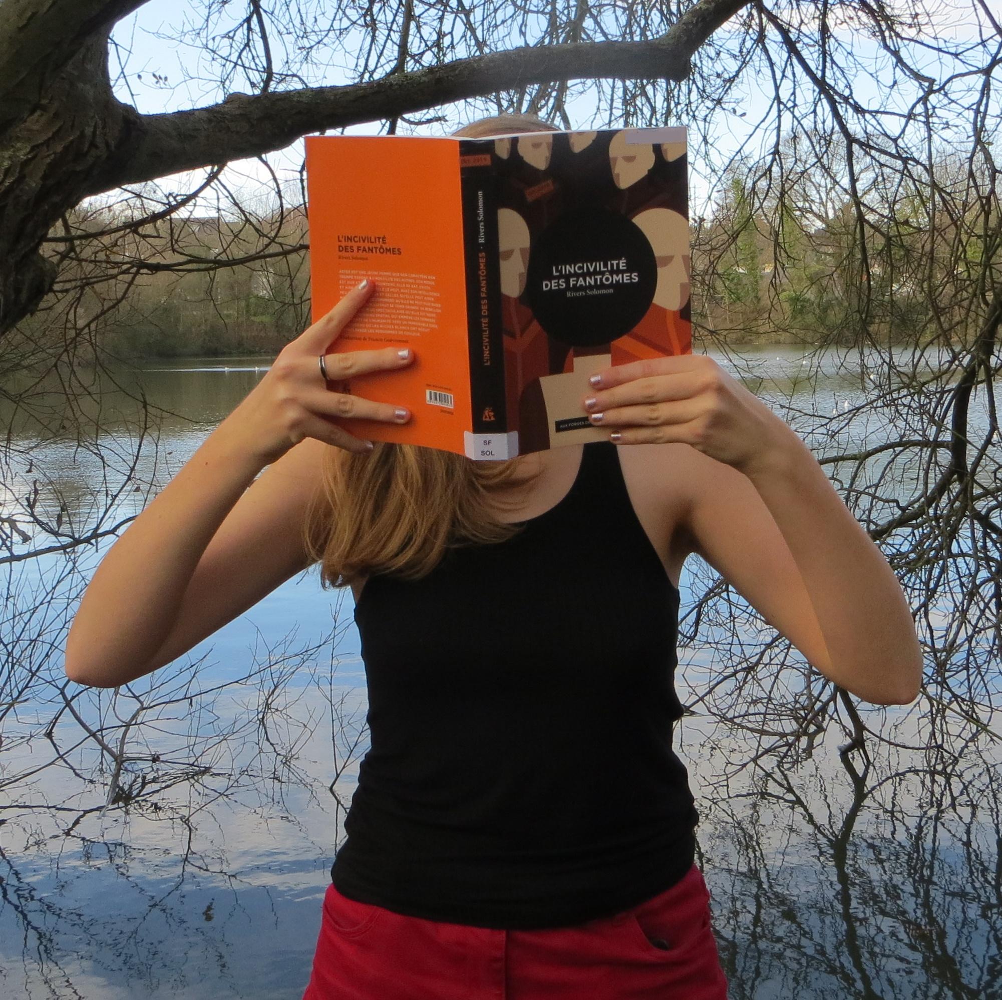 personne en débardeur noir lisant l'incivilité des fantômes devant un lac