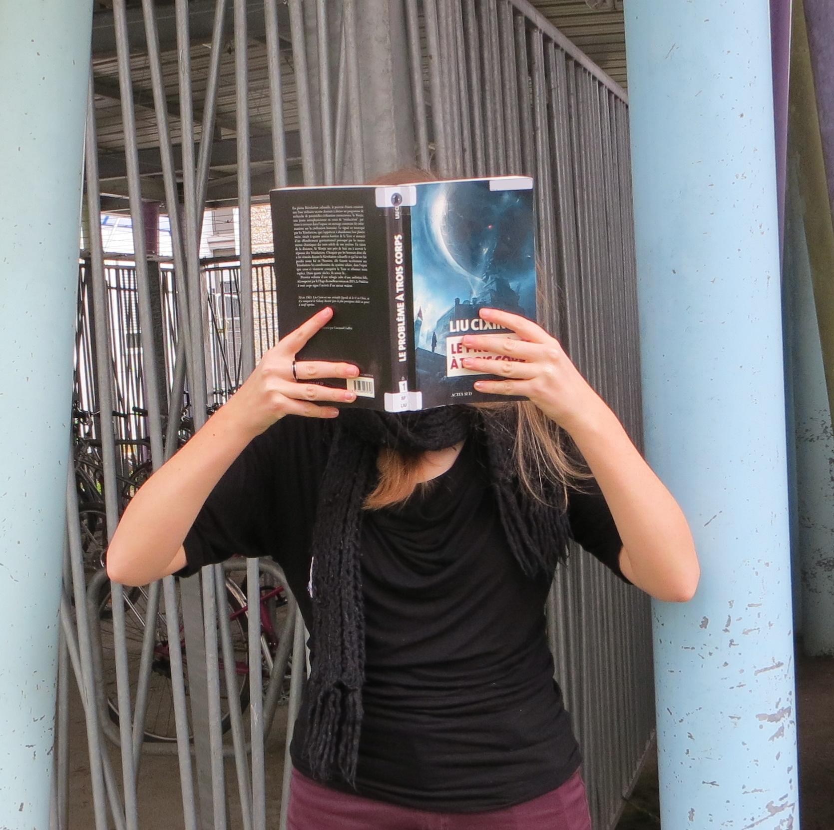 personne en noir lisant Le Problème à Trois Corps de Liu Cixin devant une grille et des piliers colorés