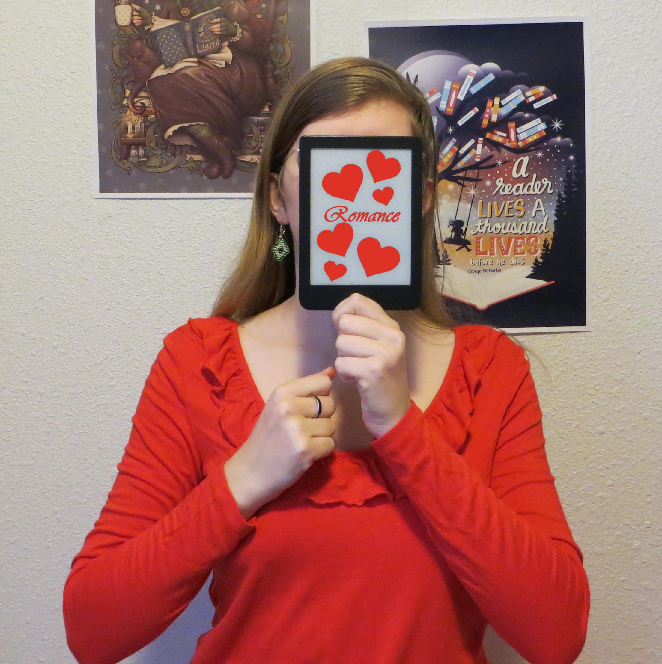 personne en rouge avec des boucles d'oreille aromantiques brandissant sa liseuse avec écrit romance et des cœurs sur l'écran