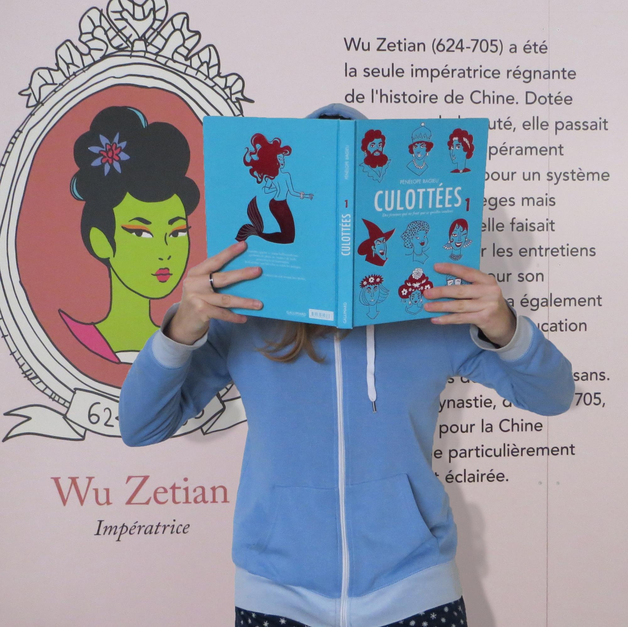 personne lisant Culottées devant la fresque murale de Wu Zetian