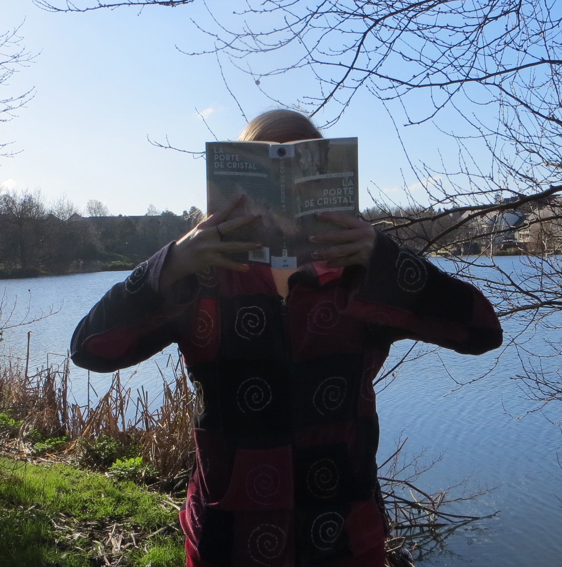 personne en gilet patchwork lisant La Porte de Cristal de N.K. Jemisin devant un lac
