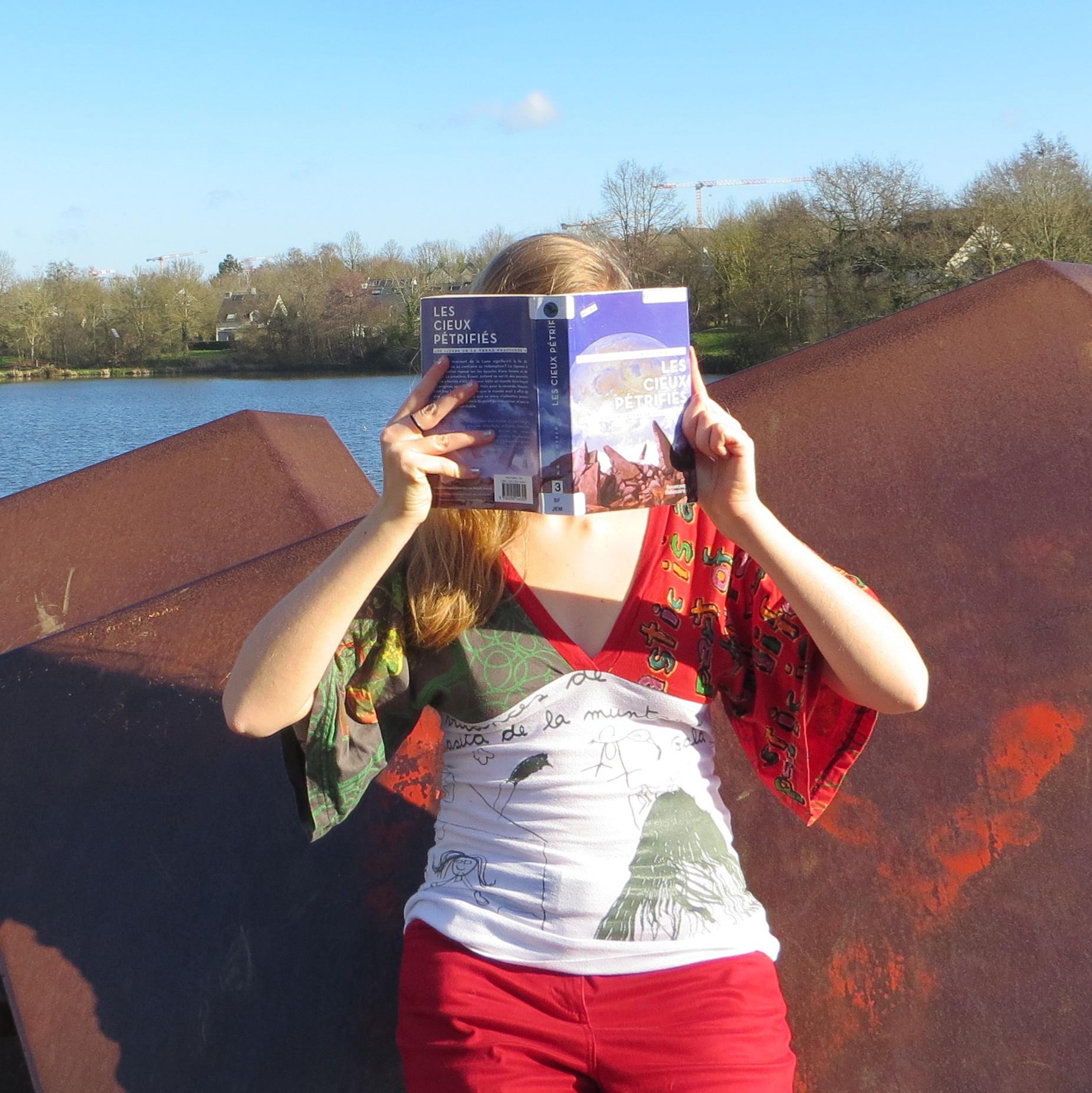 personne en t-shirt à 2 couleurs lisant Les Cieux Pétrifiés de N.K. Jemisin devant deux plaques métalliques et un lac