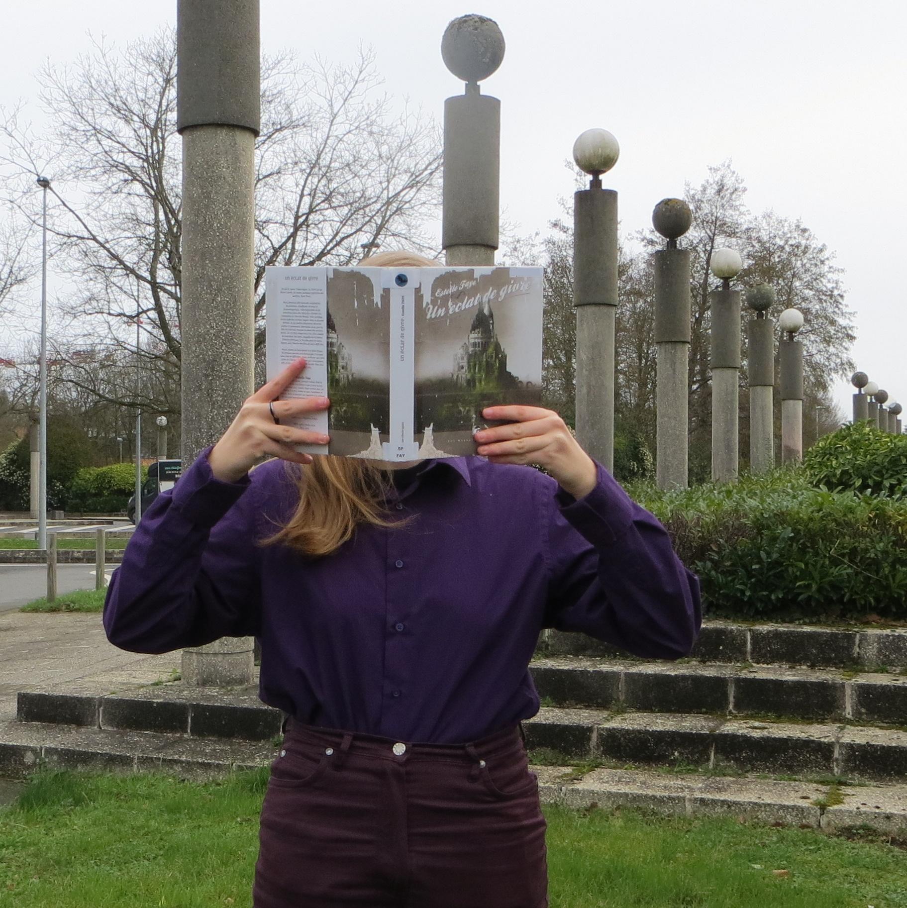 personne en chemise violette lisant Un Éclat de givre devant des colonnes