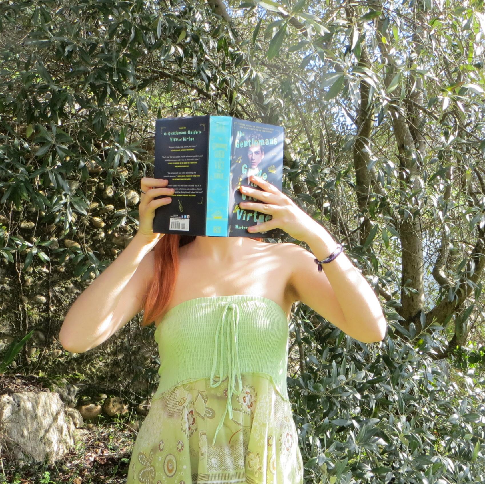 personne en robe verte lisant The Gentleman's Guide devant un olivier